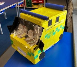 Front of large yellow handmade cardboard ambulance