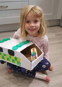 Young girl holding handmade cardboard ambulance