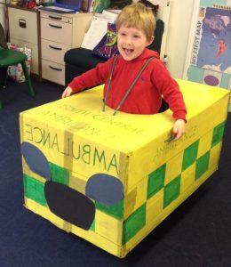 Small boy smiling inside a handmade cardboard ambulance