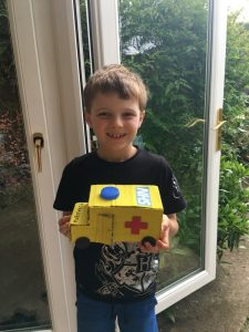 Young boy smiling and holding handmade yellow cardboard ambulance