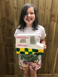 Young girl smiling and holding a handmade cardboard ambulance