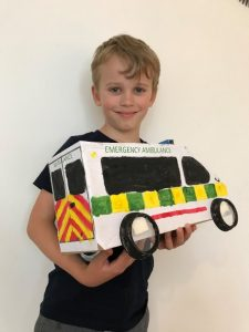Young boy smiling and holding a handmade cardboard ambulance