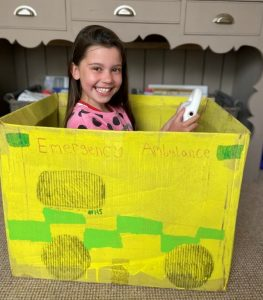 Young girl smiling and sitting inside a handmade cardboard ambulance