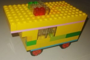 Front of small ambulance made from yellow building bricks